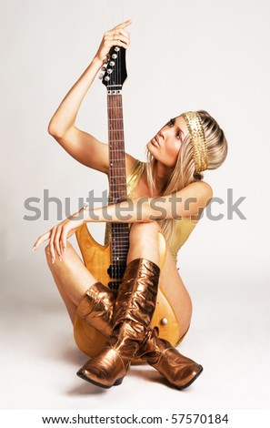 Pretty woman in golden cloting holding electric guitar