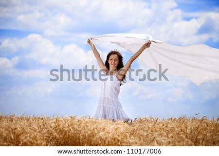 Pretty woman in golden wheat field with flying scarf