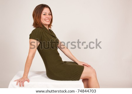 Pretty woman in green dress smiling with joy against a white background
