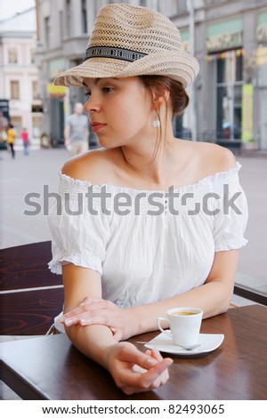 Pretty woman in hat in the street cafe - stock photo