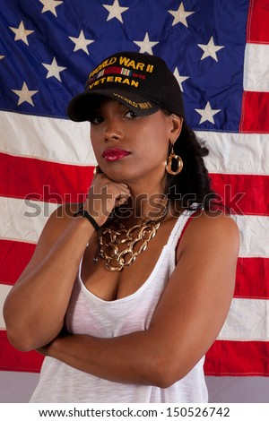 "Pretty woman in her grandfather's ""WWII Veteran"" hat, with an US flag behind her, remembering her grandfather fondly"