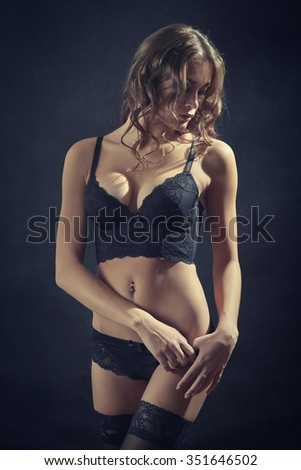pretty woman in lingerie and stockings undressing, toned image - stock photo