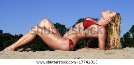 Pretty woman in red bikini arching her back on a beach on a sunny day - stock photo