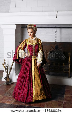 Pretty woman in red medieval costume stands near fireplace with logs and boiler.