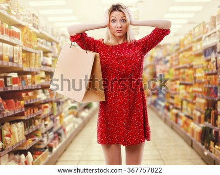Pretty woman in red with shopping bag in the supermarket. - stock photo