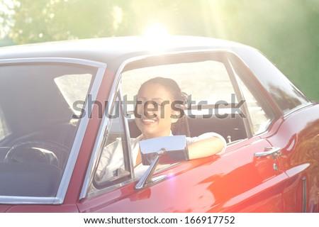 pretty woman in retro car - stock photo