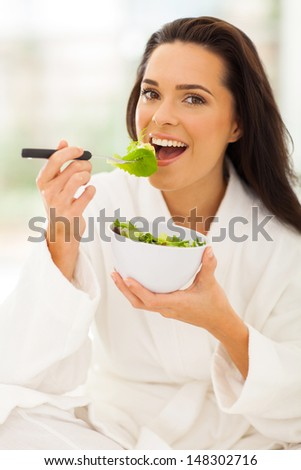 pretty woman in white bathrobe eating salad on bed - stock photo