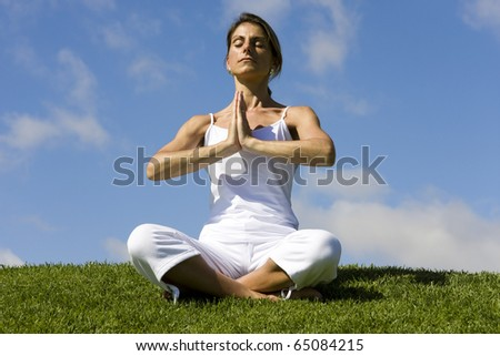 Pretty woman in white doing yoga outdoor - stock photo