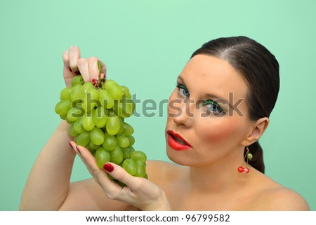 Pretty woman intending to eat bunch of grapes - stock photo