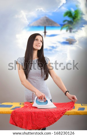 Pretty woman ironing her clothes and dreaming of a vacation  - stock photo
