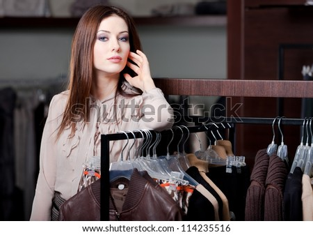 Pretty woman is in the clothing boutique - stock photo