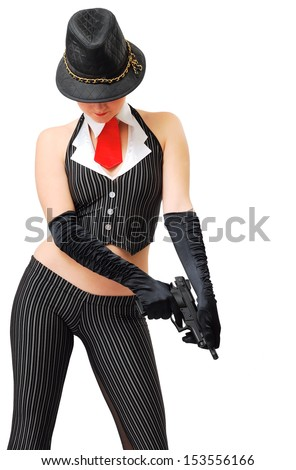 Pretty woman is reloading a pistol. She is wearing the fancy dress of gangster. Her face is hidden with black hat. - stock photo