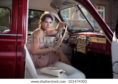 Pretty woman is sitting in the vintage car. - stock photo