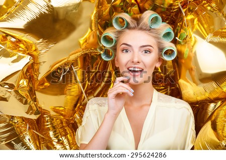 Pretty woman is standing near a lot of golden balloons. She is smiling surprisingly. The lady has curlers in her hair - stock photo
