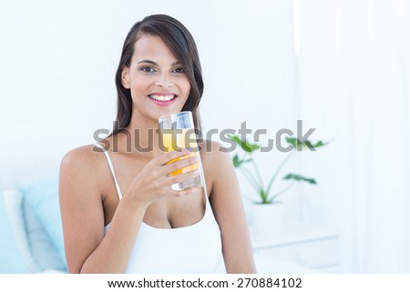 Pretty woman looking at camera holding glass of juice at home - stock photo