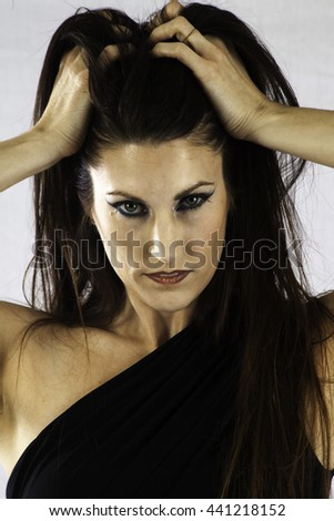 Pretty woman  looking serious  with her hands in her hair - stock photo