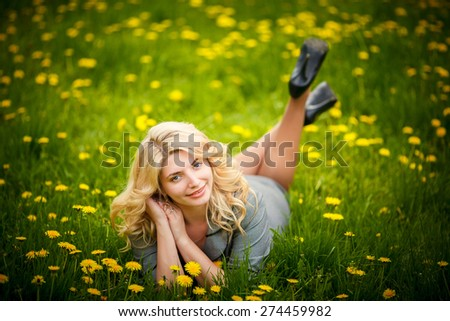 pretty woman lying down on dandelions field, happy cheerful girl resting on dandelions meadow, relaxation outdoor in springtime, vacation - stock photo