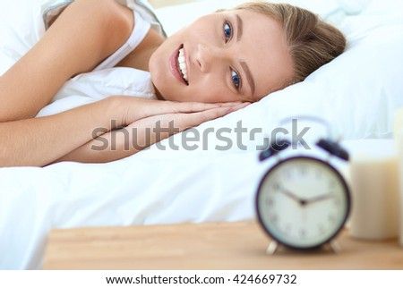 Pretty woman lying down on her bed at home