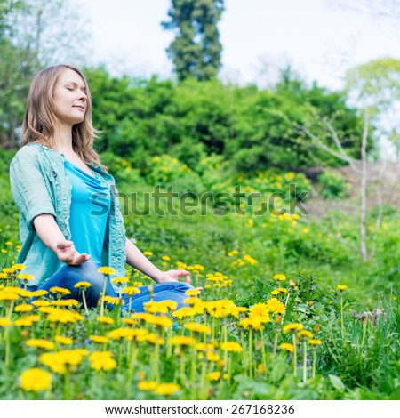 Pretty woman meditate in the park with dandelions - stock photo