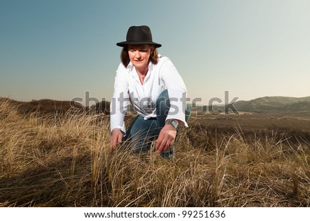 Pretty woman middle aged with hat enjoying outdoors. Clear sunny spring day with blue sky. - stock photo