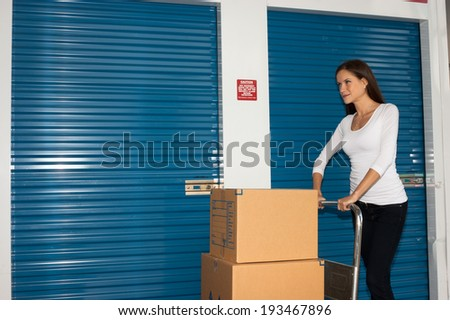 Pretty Woman Moving Cart Full Cardboard Boxes Storage Facility - stock photo