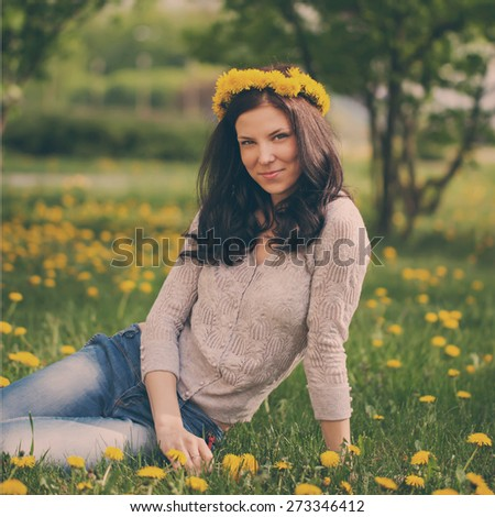 pretty woman on dandelions field, happy cheerful girl resting on dandelions meadow, relaxation outdoor in springtime, toned image - stock photo
