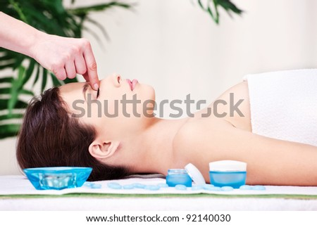 Pretty woman on forehead massage treatment in spa salon - stock photo