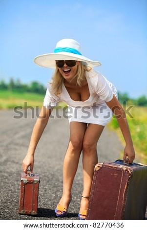 Pretty woman on the road with her baggage - stock photo