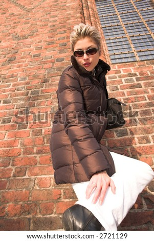 pretty woman outdoor in an old village in denmark with a wall   in red brick checking under her shoes