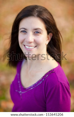 Pretty woman outdoors portrait with fall colors background  - stock photo