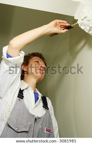 Pretty woman painting the wall - stock photo