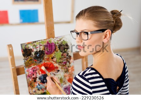 Pretty woman painting with brush and acrylic paints in artistic studio. Pensive female standing at easel with colorful picture.  - stock photo