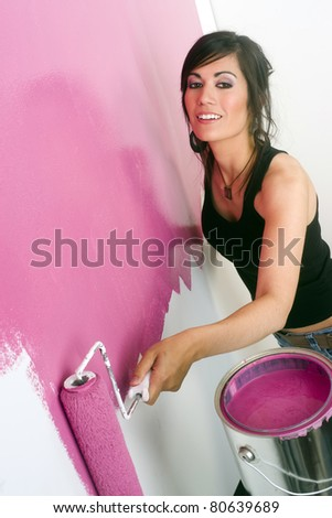 Pretty Woman Paints White Wall Pink Paint Roller Home Improvement Project - stock photo