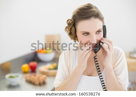 Pretty woman phoning with her telephone in the kitchen at home - stock photo