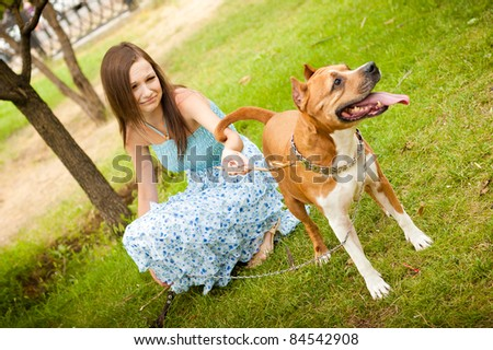 pretty woman playing together with dog