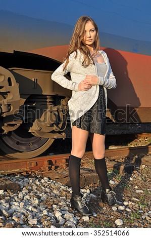 Pretty woman posing at train station - stock photo