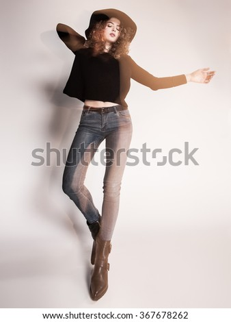 pretty woman posing in denim pants and boots and black hat - intentional motion blur - stock photo