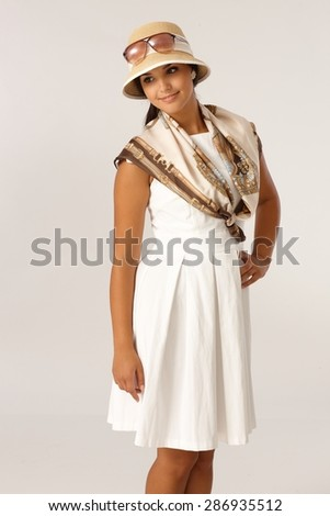 Pretty woman posing in summer dress and hat, smiling. - stock photo