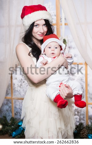 Pretty woman posing with her baby dressed as Santa