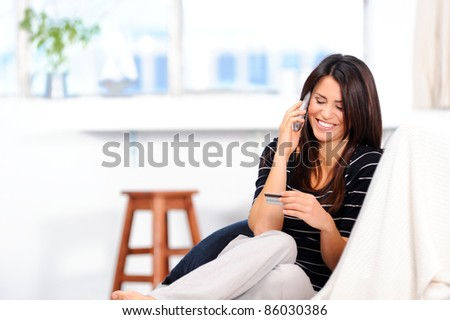 Pretty woman reads her credit card information for payment - stock photo