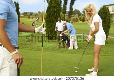 Pretty woman ready for holing on the green, smiling. - stock photo