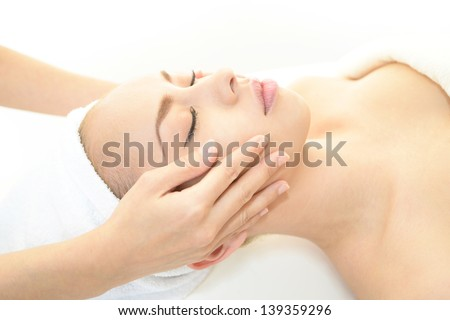 Pretty woman receiving facial massage - stock photo