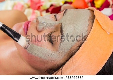 Pretty woman receiving facial massage at beauty salon - stock photo