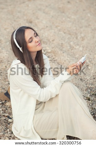 Pretty woman relax listening music with phone against sea sand backdrop. - stock photo