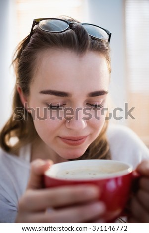 Pretty woman relaxing on couch with coffee in the living room - stock photo