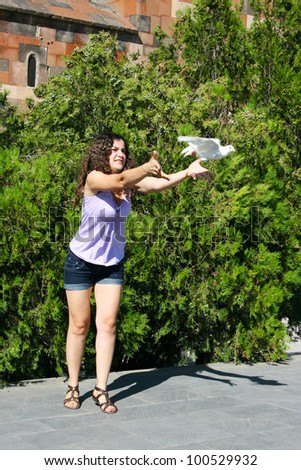 Pretty woman releasing a pigeon at Khor Virap church in Armenia.