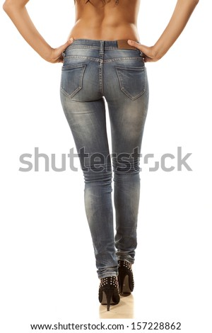pretty woman's legs and buttocks in tight jeans - stock photo