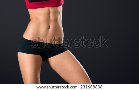 Pretty woman's torso close up with strong and perfect abs on black background - stock photo