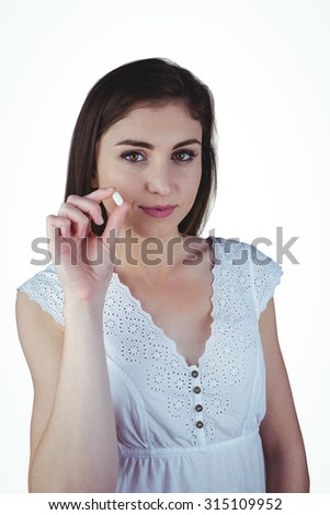 Pretty woman showing white pill on white background - stock photo