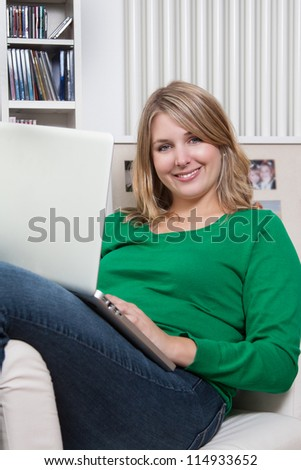 Pretty woman sits on an armchair with a notebook on her lap - stock photo
